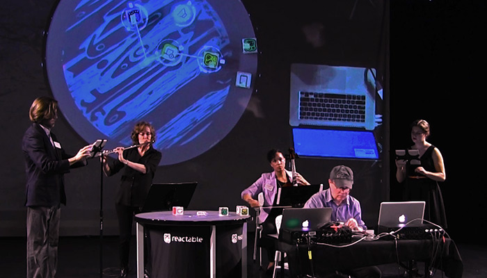 Five musicians onstage, from left a man uses an iPad, a woman plays flute, a seated woman plays cello, in foreground a man sits at a laptop, and on far right a woman uses an iPad