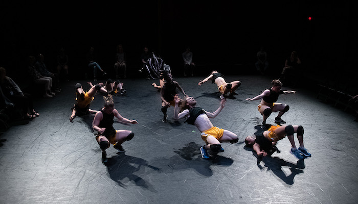 A group of nine dancers wearing yellow shorts and black crop tops in a circle on a low-lit stage, all squatting or in other positions that place them close to or on the floor. An audience can be seen around them past the edge of the stage