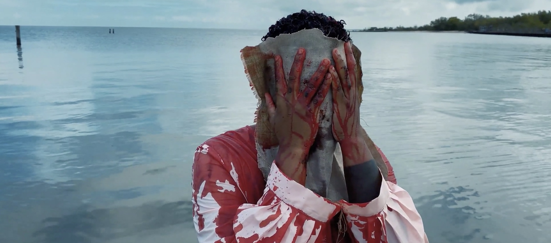 A black trans woman standing in Lake Pontchartain in a white tunic covered in blood uses a towel to wipe blood from their face