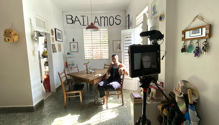 Choreographer Awilda Rodriguez Lora sits at a small, square dining table in her living and performance space La Rosario in Puerto Rico. A video camera recording her can be seen to the right in the forefront of the frame.