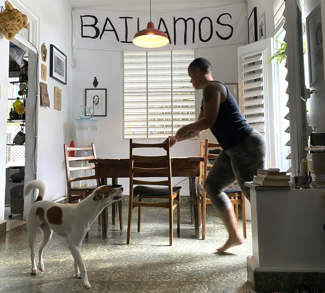 Choreographer Awilda Rodriguez Lora plays with her white, brown-spotted dog in her living and performance space La Rosario in Puerto Rico.