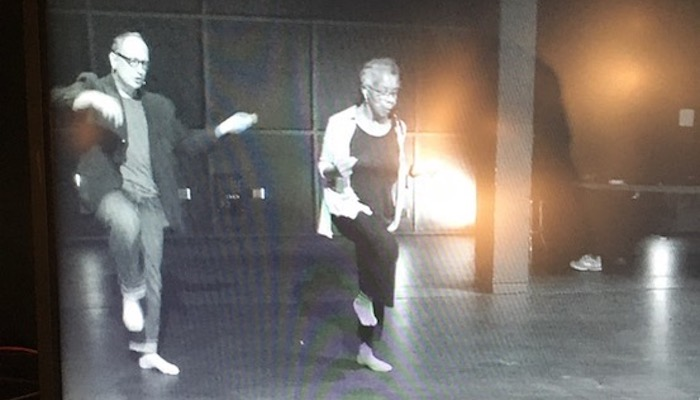 Dancers Paul Lazar and Bebe Miller rehearsing on an empty stage, as seen through a TV monitor