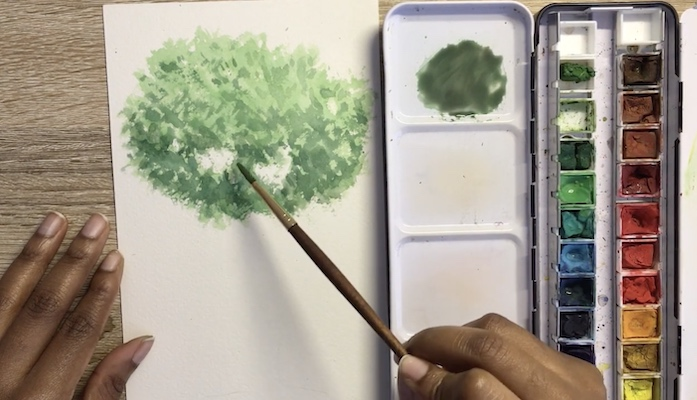 On a wood work surface with an open container of watercolor paints, a black woman's hands apply green paint to white paper, creating the look of a tree top