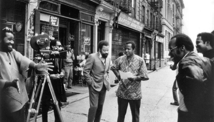 Black-and-white archive image of filmmaker William Greaves with a group of Black men shooting a film on a street full of storefronts