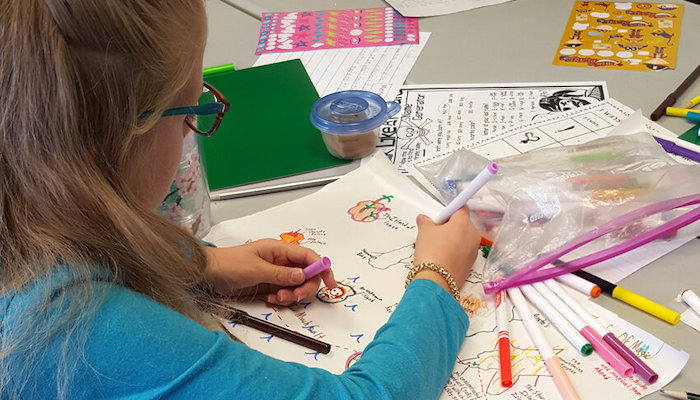 A young blonde girl in a green shirt and glasses, seen partly from behind as she draws in a sketchbook on a table covered in papers and art supplies