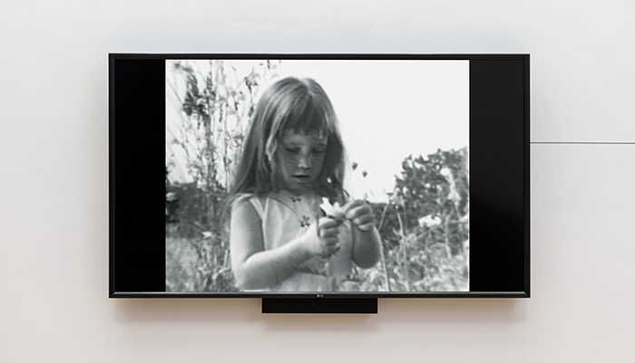 A tv mounted to a gallery wall displays a black and white image of a young girl holding a flower.