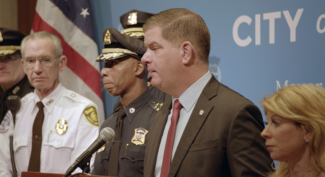 Boston Mayor Martin Walsh speaks at a podium along side police officers and city officials