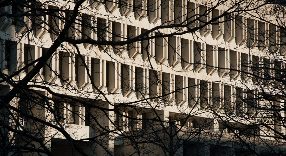 The front of a 1970s era city building with brutalist concrete ornamentation in daylight