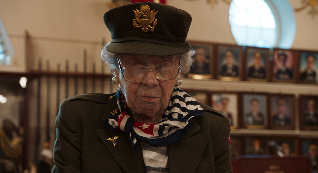 An elderly woman in military garb in front of a wall of officer photos