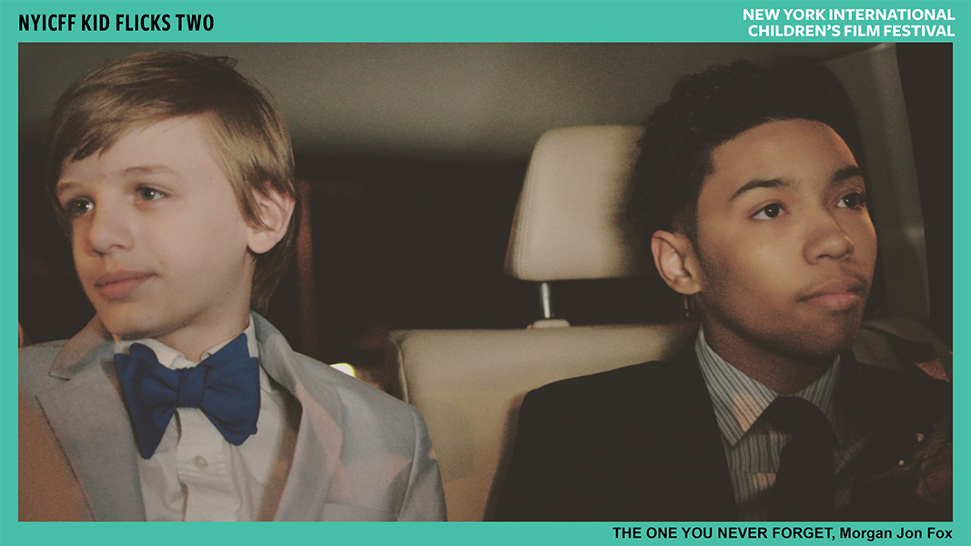Two young boys in suits and ties sit in the back seat of a car and look out opposite windows.