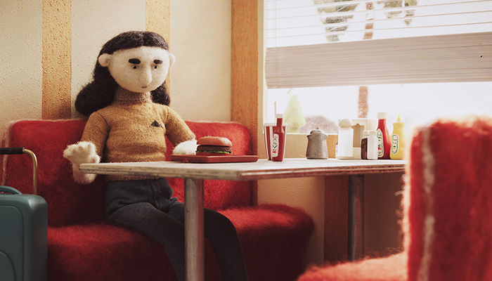 A woman character, made of felt, stares at the burger she ordered with her suitcase by her side.