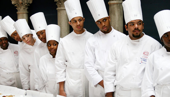 A row of people are lined up wearing chef hats.