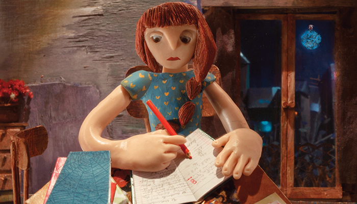 A woman, constructed from clay, sits at a desk and writes in a journal.