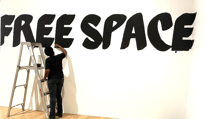 "Artist Lisa McLymont is seen from behind, with a ladder beside her, paints the words ""free space"" in black on a white wall"