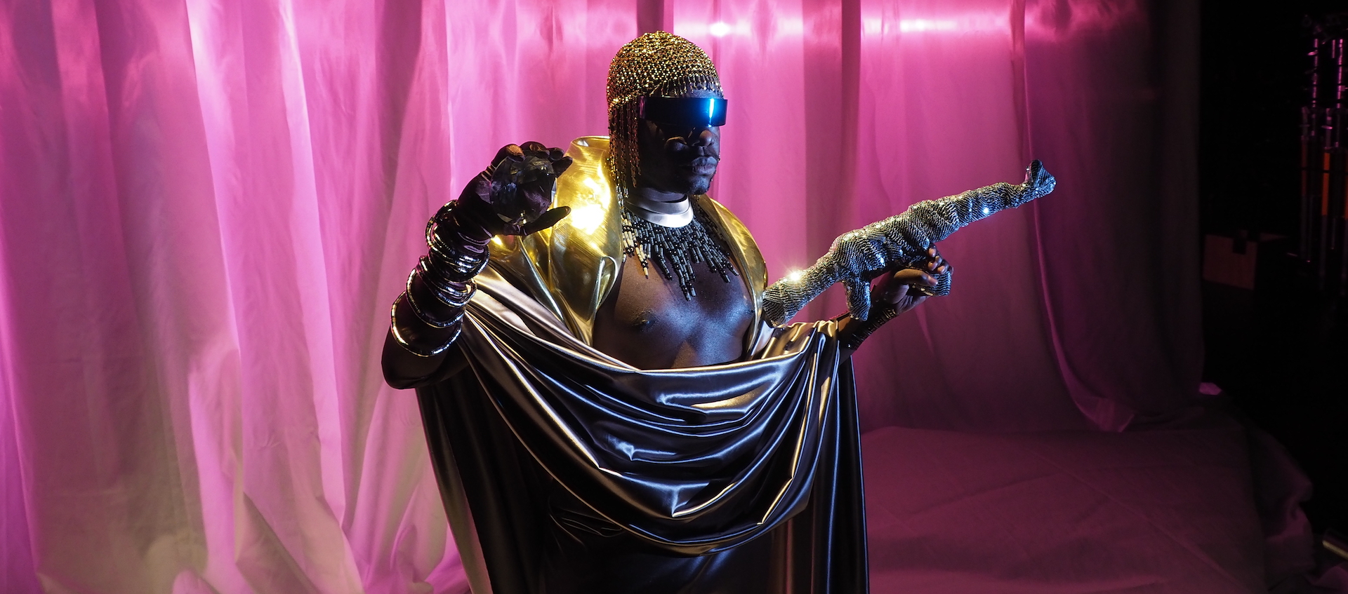 Artist Jaamil Olawale Kosoko stands on a stage with a pink fabric backdrop, wrapped in a gray silk sheet, wearing a metallic gold scarf, bejeweled crocheted beanie and gloves with bangle bracelets. In his left hand he holds what appears to be a rifle wrapped in sequined fabric