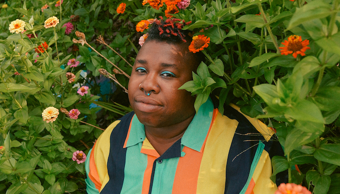 Singer-songwriter Sharon Udoh, wearing a bright collared shirt with vertical stripes, standing nestled in a large bush with orange and yellow flowers