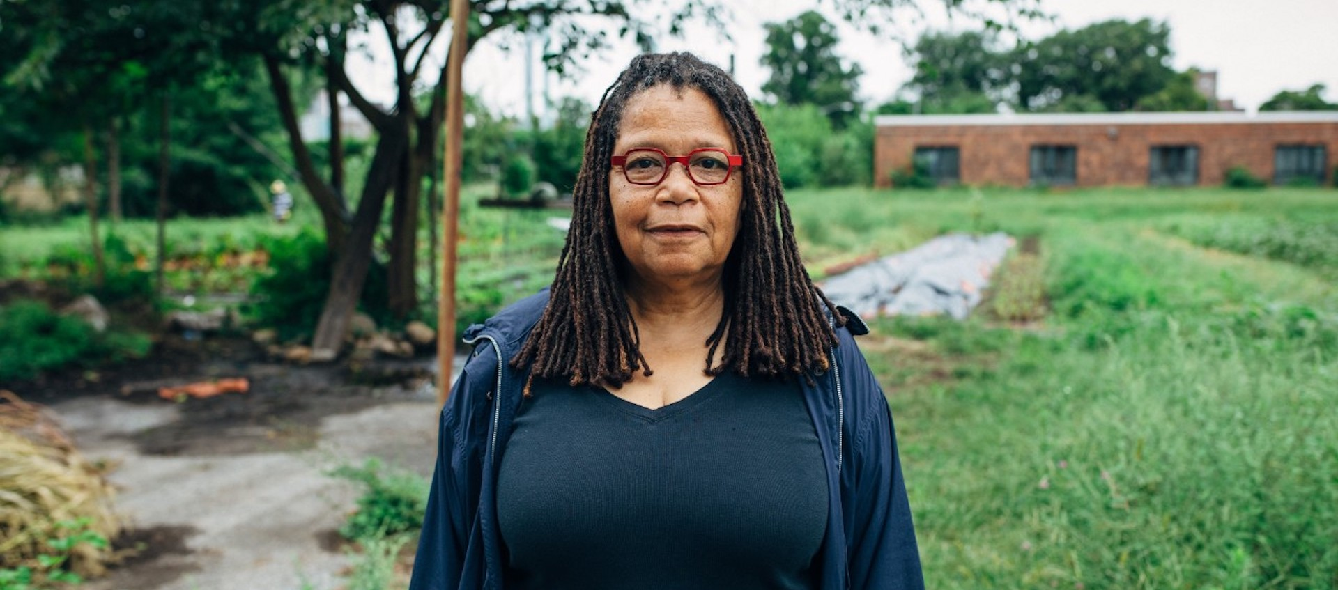 Artist and activist Linda Goode Bryant, wearing a dark blue shirt and glasses, stands outside in a grassy area with a vegetable garden to the side and a brick building in the distance