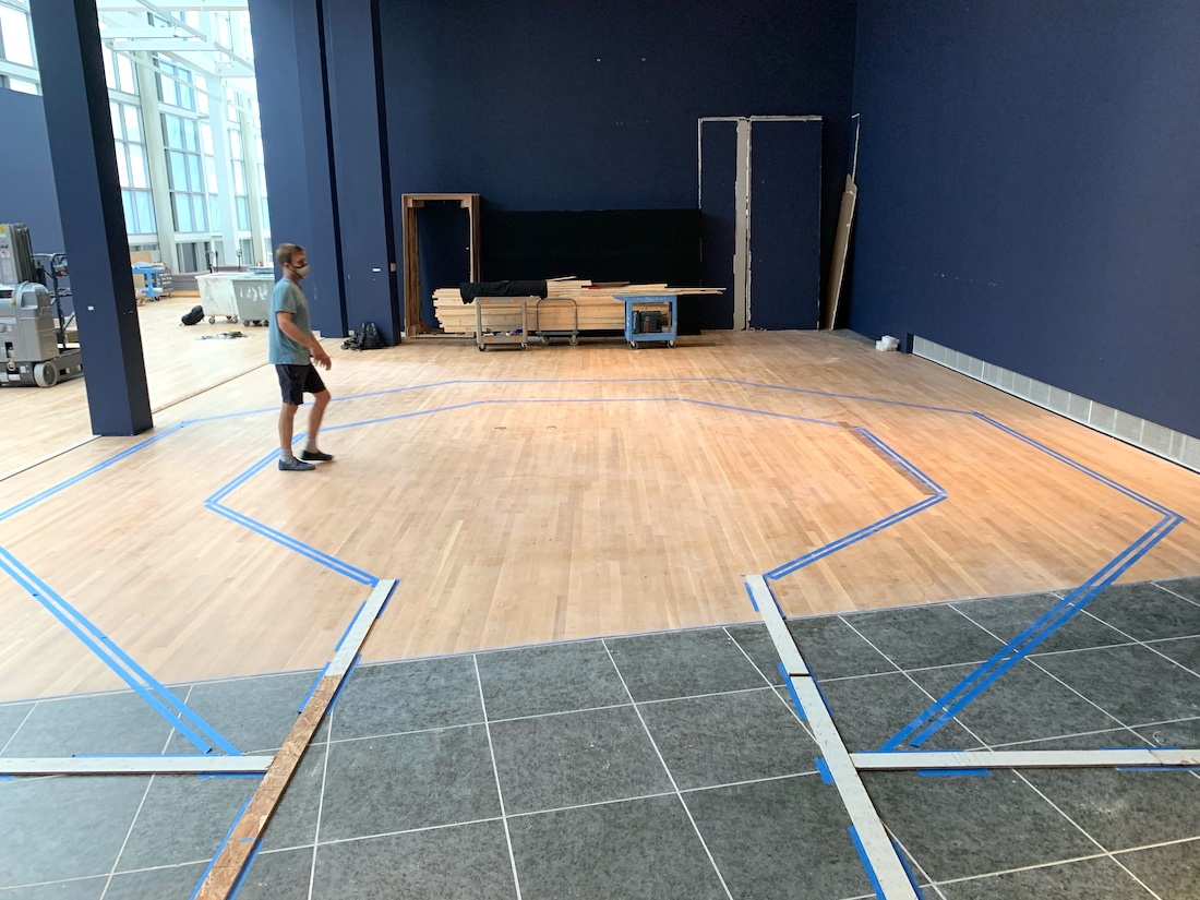 A preparator at the Wexner Center for the Arts stands in one of the gallery spaces, surrounded by tape lines on the floor that mark out the eventual layout of the installation Taryn Simon: Assembled Audience