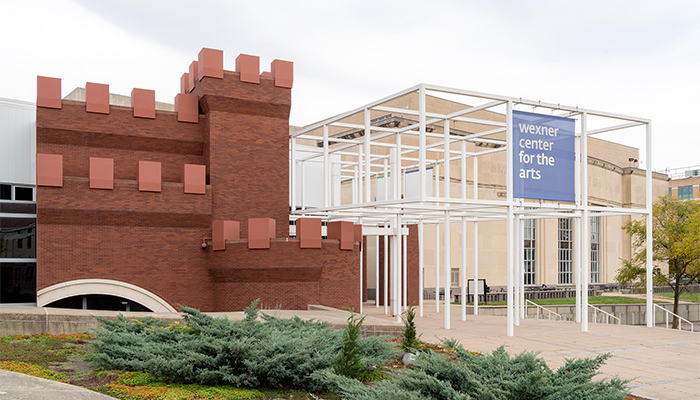 The Wexner Center's exterior features crenellated, castle-like brick towers and contrastingly spare modular core with a projecting grid-like metal framework.