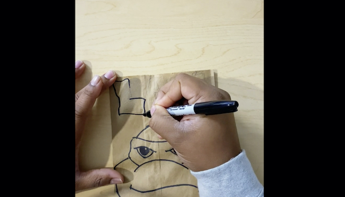 The hands of artist Alexander Chisley are seen drawing text with Sharpie marker above a drawing of a Teenage Mutant Ninja Turtle on a paper bag