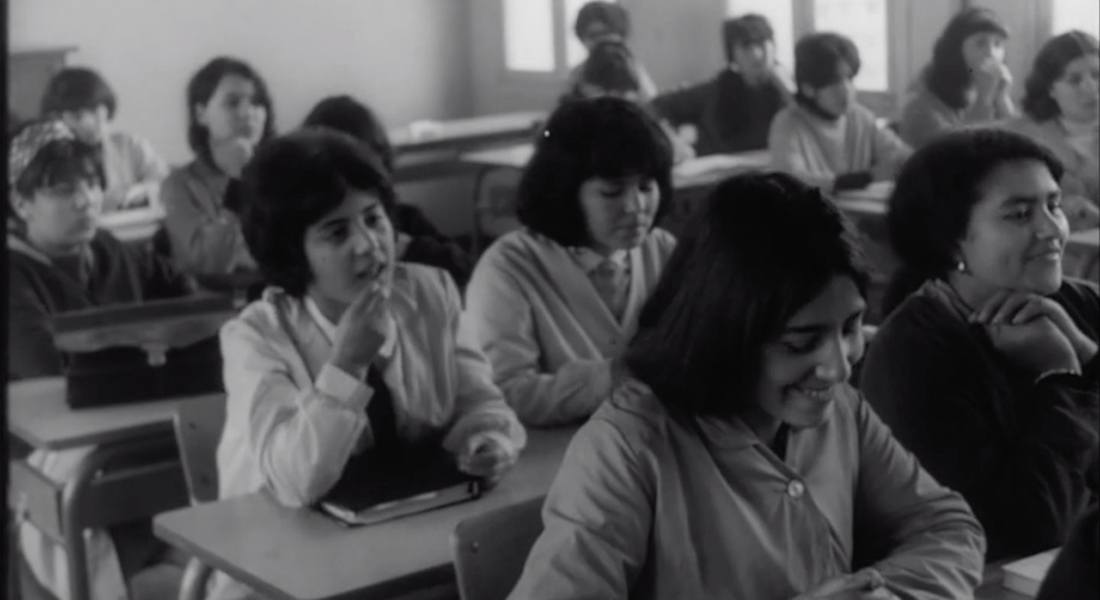 multiple female students sitting behind their desks in the classroom