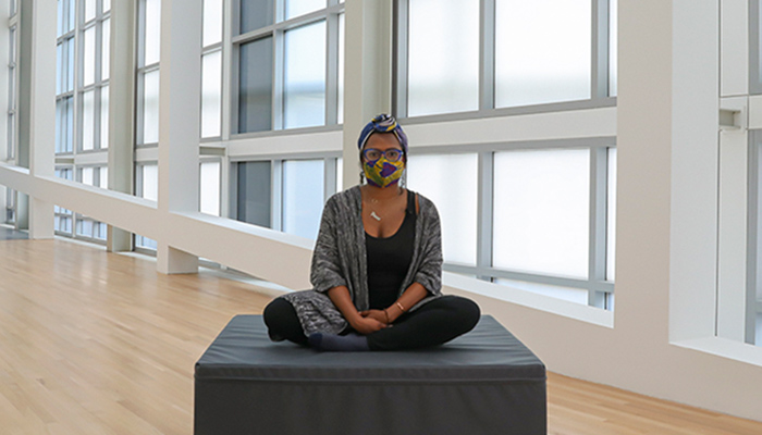 A woman sits on a foam block in the center of an empty gallery space.