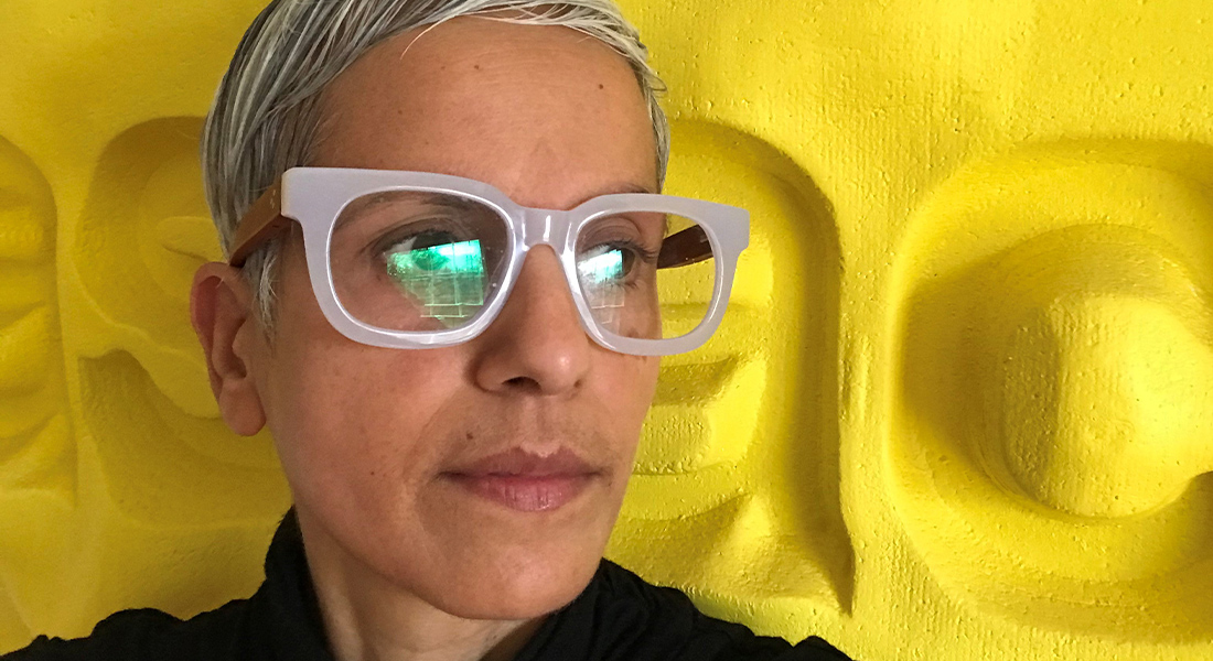Image of Sandhya Kochar wearing eyeglasses and standing in front of a yellow background