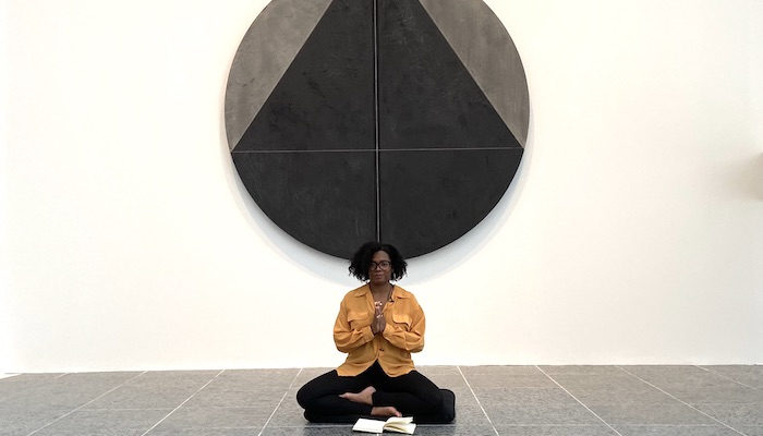 Monique McCrystal sits on the tile floor of the Wexner Center for the Arts galleries with her hands in prayer pose, underneath a round abstract painting in black and gray by Torkwase Dyson