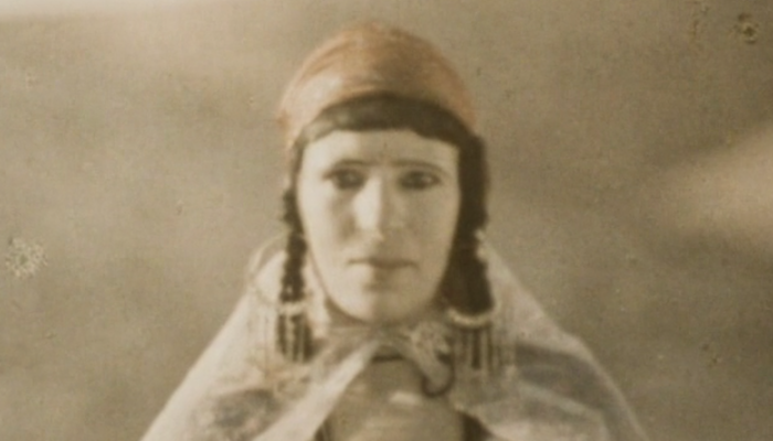 Sepia tone mage of a woman facing the camera wearing a head scarf, braids, large hoop earrings and a cape from Assia Djebar's 1982 French documentary Zerda and the Songs of Forgetting