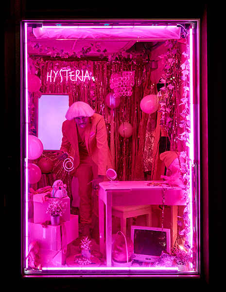 A pink tinted image. Raja Father Kelly stands in the center of the frame. Behind Kelly is the word HYSTERIA in neon. To Kelly's right is a desk with a computer underneath it.