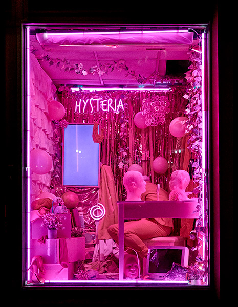 A vertical image of a room in a pink tint. Raja Feather Kelly is seated and the wall behind them is covered in tinsel and balloons.