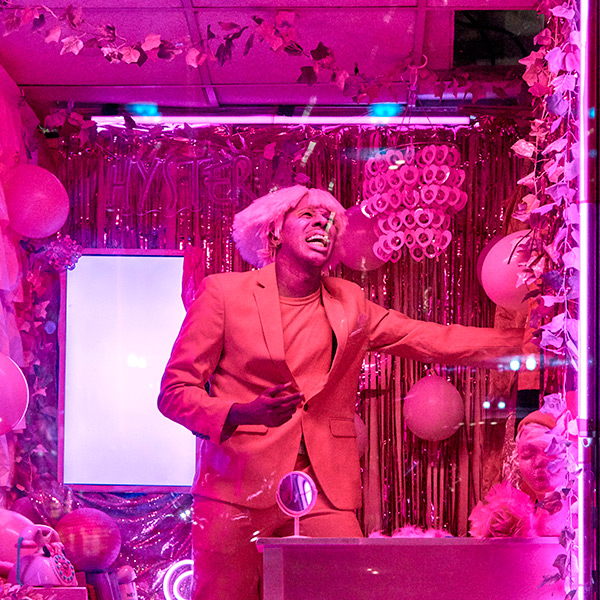 A hot pink image with Raja Feather Kelly in the center of the frame standing on a stage. Kelly is in a pink jacket and wig with arm outstretched. Kelly appears to be singing and behind Kelly are balloons and tinsel covered backdrop.
