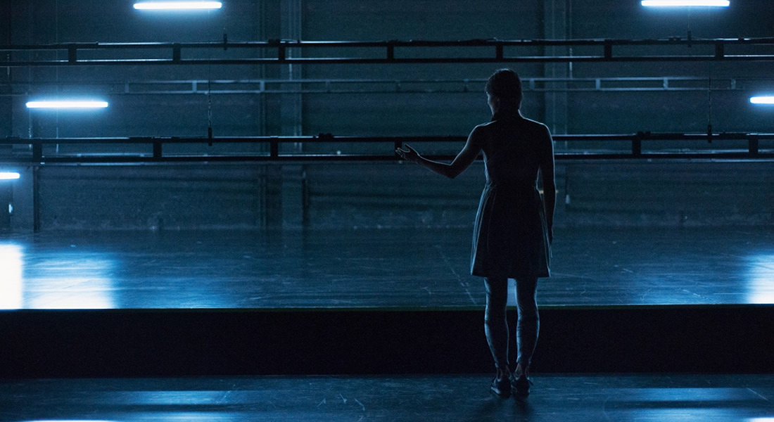 An image of a solitary dancer on a stage lit in blue from Radouan Mriziga's movement work 7