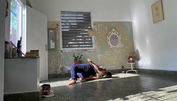 Movement artist Awilda Rodriguez Lora lies on the floor of her home La Rosario in Puerto Rico, her knees bent and her back arched with her left hip lifted off the floor so she's facing away from the camera